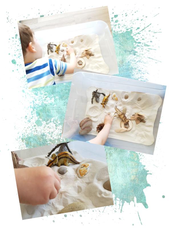 Kind spielt mit Sand, Holz und Dinos in einer transparenten Kiste